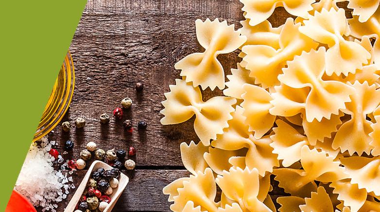 Pasta liegt ungekocht auf braunem Holzbrett