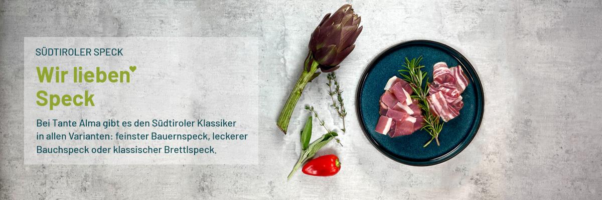 Südtiroler Speck auf Teller, als Dekoration liegt eine Artischocke und Paprika dabei
