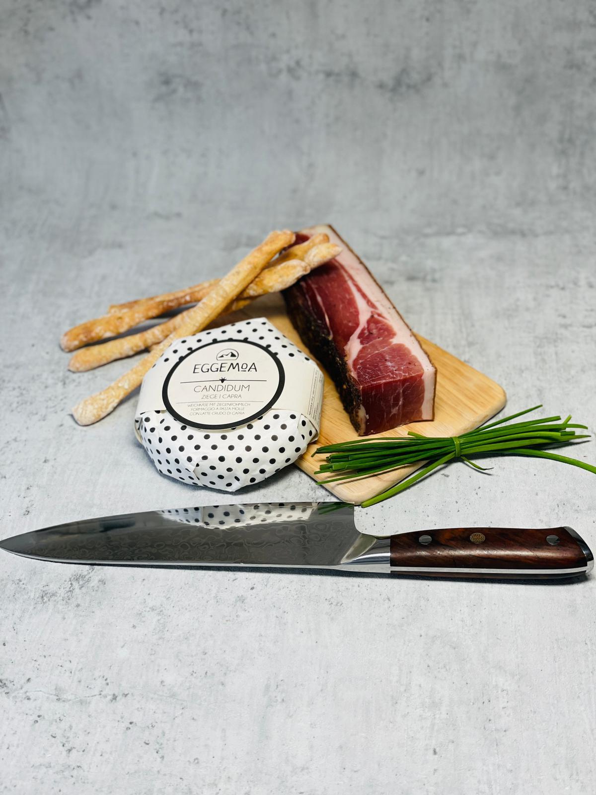 Ein Messer liegt vor Speck, Käse, Lauch und einigen Grissinis
