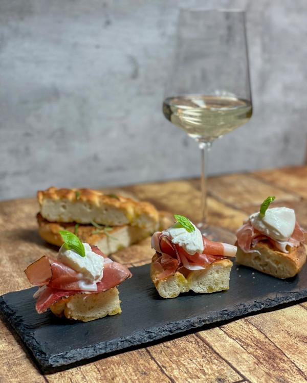 Südtiroler Speck angerichtet auf Baguette, im Hintergrund steht ein Glas Weißwein